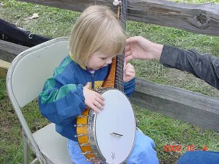 A small child happily holding a banjo